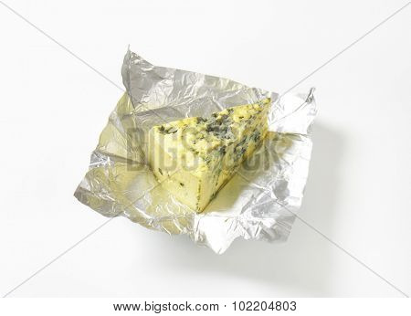 Wedge of French blue cheese on foil