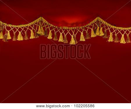 Close up of golden tassels hanging over red classic curtain.