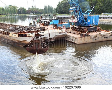 NYMBURK CZECH REPUBLIC - SEPTEMBER 20, 2015: Dredging boat cleaning bottom of Elbe (Labe) River nearby Hydroelectric plant. Very important work for energetic industry and shipping on river.