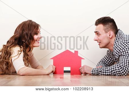 Couple Lying On The Floor Holding Paper House