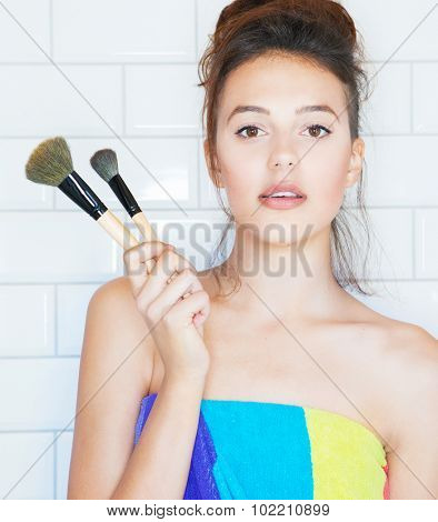 Applying make up concept, young attractive woman covered with towel with cosmetic brush