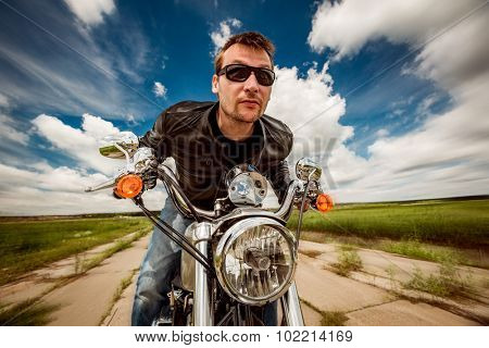 Biker man wearing a leather jacket and sunglasses sitting on his motorcycle and racing on the road.