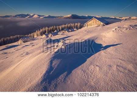 Winter landscape in the morning. Wooden houses in the mountains