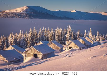 Winter landscape with wooden houses in the mountains. Sunny morning. The village of shepherds