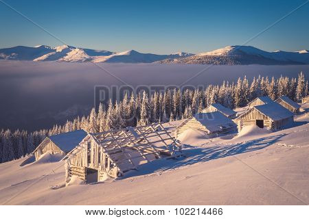 Winter landscape with old wooden houses in the mountains. Sunny morning. The village of shepherds