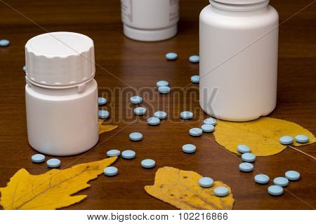 Blue pills and medicine bottle on wooden background