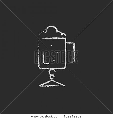 Glass mug with foam hand drawn in chalk on a blackboard vector white icon isolated on a black background.