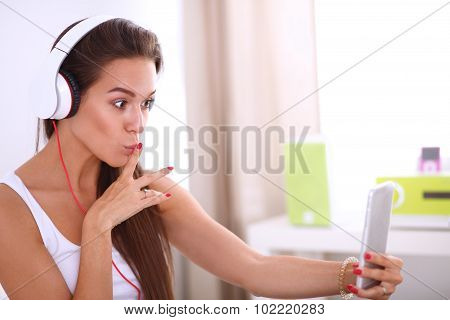 Young beautiful woman in bed  taking a selfie while listening to music