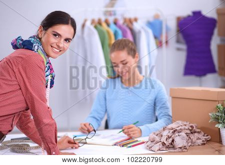 Clothes designer with an assistant at work