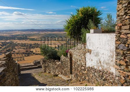 Europe, Portugal, Evora, Monsaraz village - view from a traditional street to the fields of