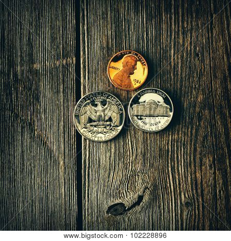 Three US cent coins over wooden background