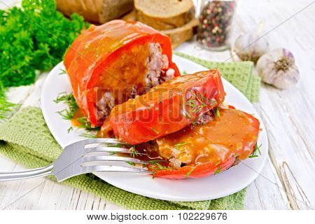 Pepper stuffed meat with sauce and fork in plate on table