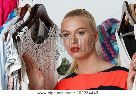 Beautiful Thoughtful Blonde Woman Standing Inside Wardrobe Rack