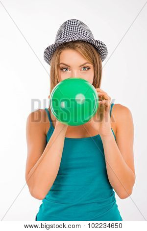 Attractive Girl Inflating A Green Balloon