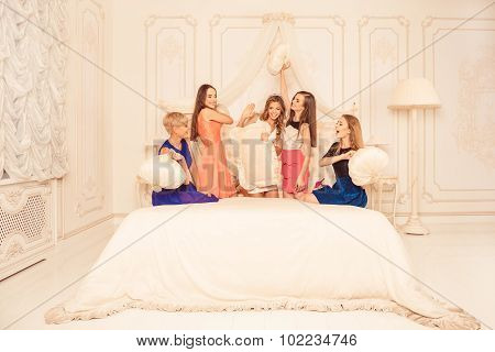 Cheerful Girls Staged A Pillow Fight On The Bed