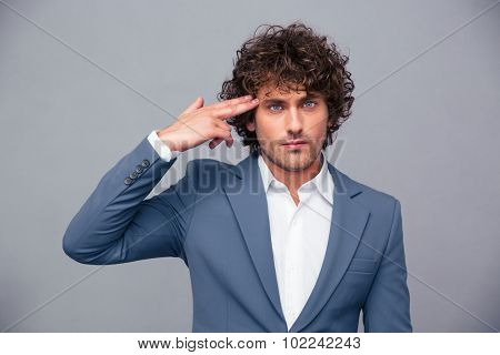 Portrait of a handsome businessman doing gun gesture at head over gray background