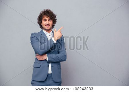 Portrait of a smiling businessman pointing finger away over gray background and looking at camera