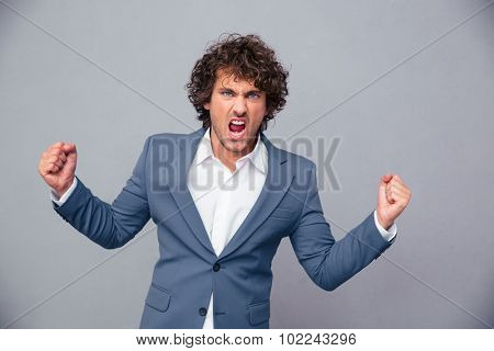 Portrait of angry businessman shouting over gray background