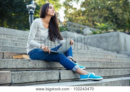 Portrait of a thoughtful female student sitting on the city stairs and using laptop computer outdoors