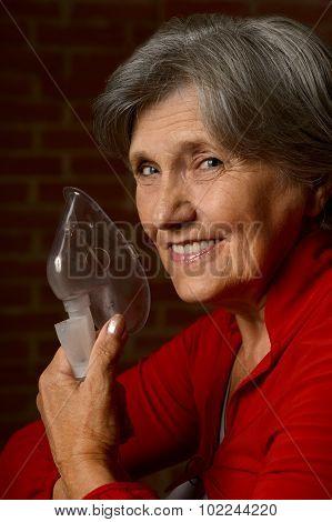 Older sick woman with inhaler