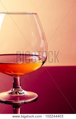 Snifter Of Brandy In Elegant Typical Cognac Glass On Purple Colored Light Disco Background