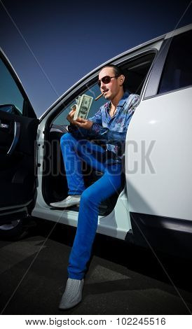 Man with cigar and dollars near the car