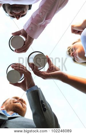 Directly below shot of businesspeople holding disposable cups against clear sky