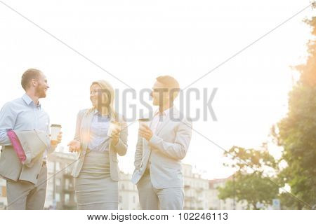 Happy businesspeople with disposable cups talking against clear sky on sunny day