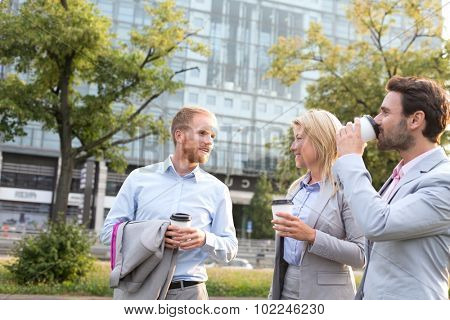 Businesspeople with disposable cups conversing in city