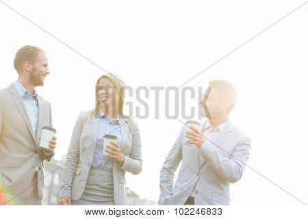 Businesspeople with disposable cups talking against clear sky on sunny day