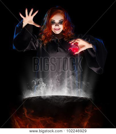 Young witch with red potion isolated
