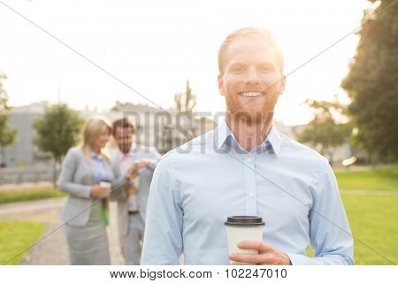 Portrait of happy businessman holding disposable cup with colleagues standing in background