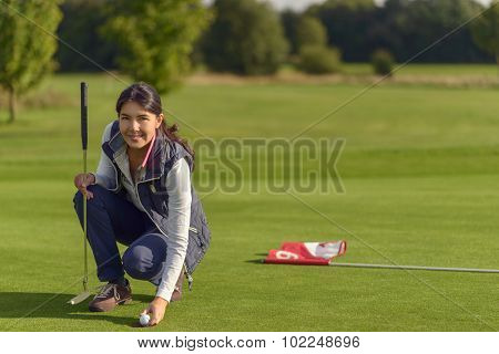 Female Golfer Pickung Up A Golf Ball