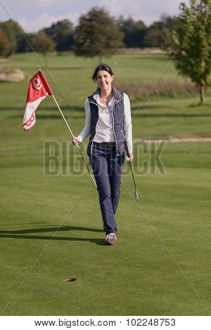 Female Golfer Holding The Flag From The Hole