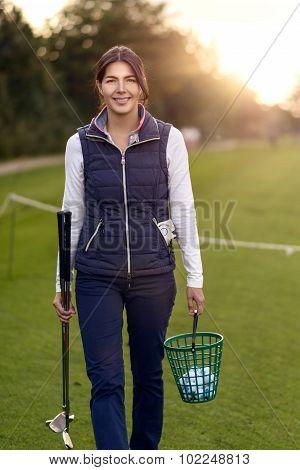Woman Golfer Carrying Balls On A Driving Range