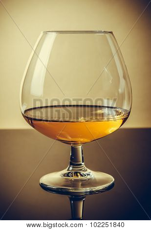 Snifter Of Brandy In Elegant Typical Cognac Glass On Old Fashion Style Background