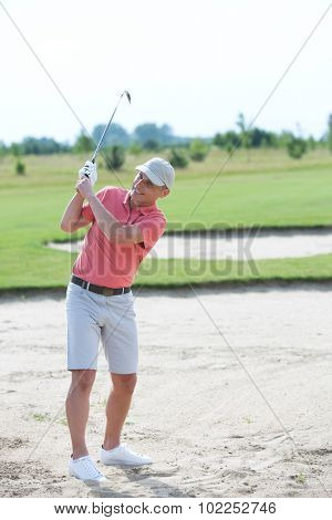 Middle-aged man swinging at golf course
