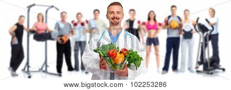 Doctor with vegetables and group of healthy fitness people
