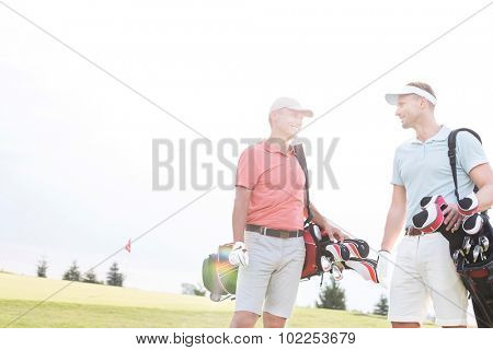 Smiling men talking at golf course against clear sky