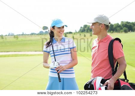 Happy male and female golfers communicating at course