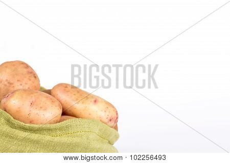 pure potato tubers in a sack isolated on white background