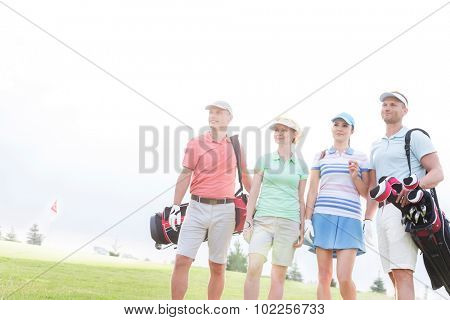 Male and female friends standing at golf course against clear sky