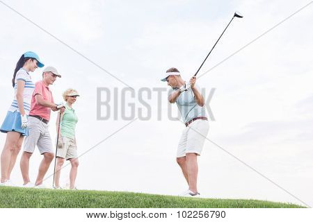 Friends looking at man playing golf against sky