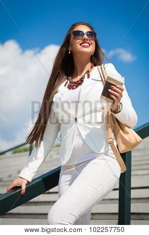 Beautiful young businesswoman with a disposable coffee cup