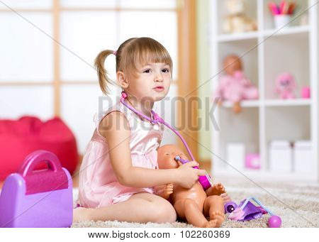 Little girl playing with dolls in hospital