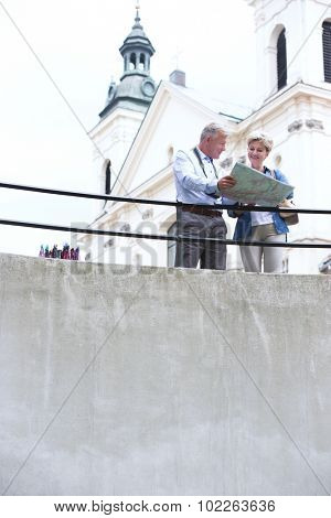 Middle-aged couple reading map by railing outside church