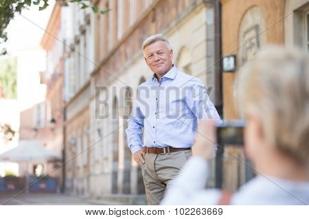 Middle-aged woman taking picture of man in city