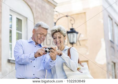Happy middle-aged couple looking at pictures on digital camera in city