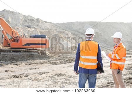 Supervisors standing at construction site against clear sky