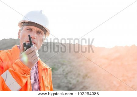 Confident supervisor using walkie-talkie on construction site against clear sky